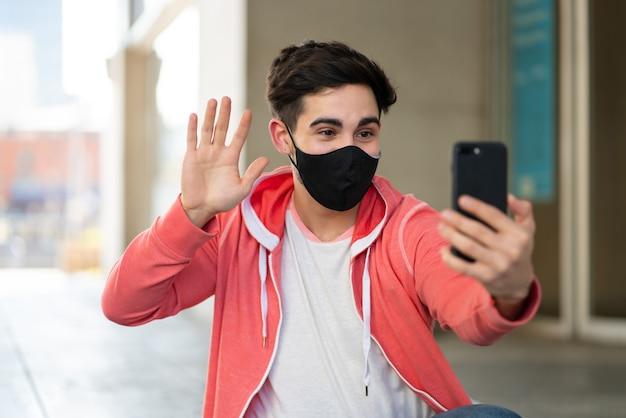 通りで屋外に座っている間携帯電話でビデオ通話をしている若い男の肖像画。新しい通常のライフスタイルのコンセプト。アーバンコンセプト。