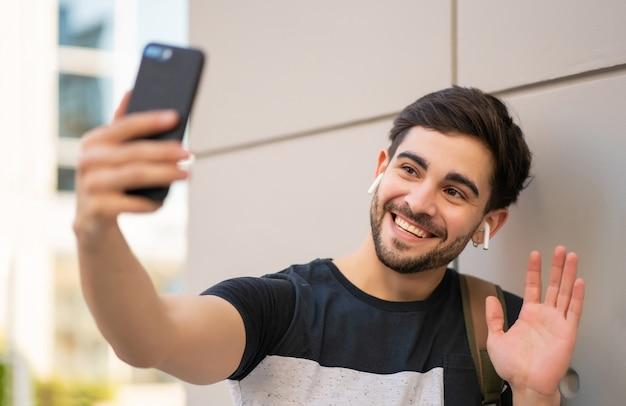 야외에서 서있는 동안 휴대 전화에 화상 통화를하는 젊은 남자의 초상화. 도시 개념.