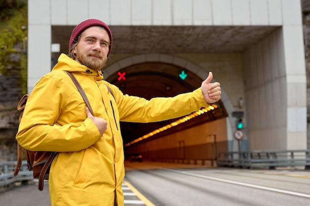 旅行のために通過する車を捕まえようとして、全国をヒッチハイクしている若い男の肖像画。バックパックを背負った黄色いコートを着た白人の流行に敏感な男性が南にヒッチハイクしました。