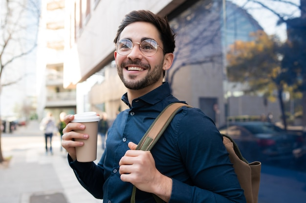 通りで屋外を歩きながらコーヒーを持っている若い男の肖像画。アーバンとライフスタイルのコンセプト。