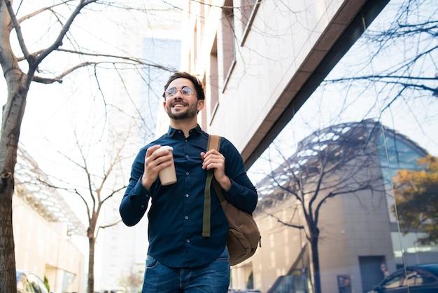 거리에서 야외에서 걷는 동안 커피 한 잔을 들고 젊은 남자의 초상화