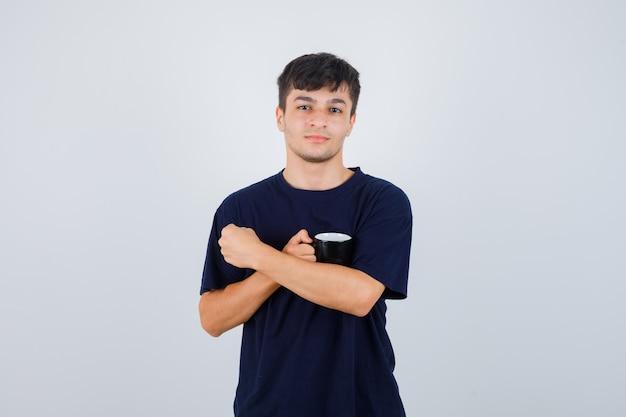 Портрет молодого человека, держащего чашку чая в черной футболке и уверенно выглядящего, вид спереди