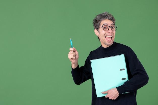 녹색 배경 교사 수업 비즈니스 작업에 문서를 들고 젊은 남자의 초상화