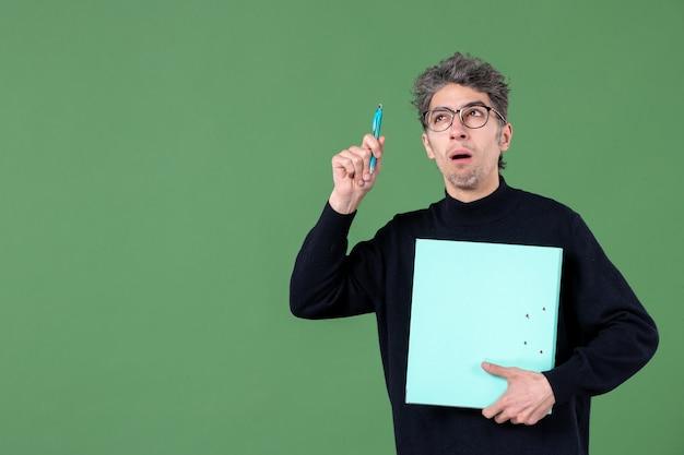 녹색 배경 교사 수업 작업에 문서를 들고 젊은 남자의 초상화