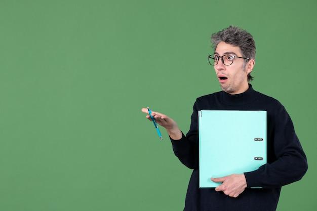 녹색 배경 작업 교사 사업에 문서를 들고 젊은 남자의 초상화