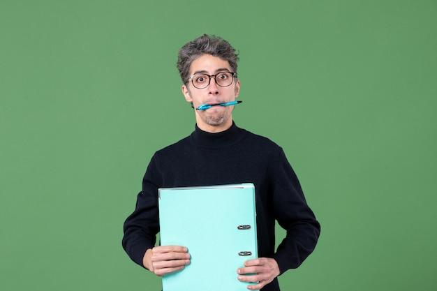 녹색 배경 작업 수업 비즈니스 교사 직업에 그의 입 스튜디오 촬영으로 문서와 펜을 들고 젊은 남자의 초상화