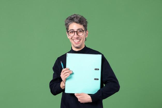 녹색 배경 비즈니스 교사 직업 수업에 문서 스튜디오 촬영을 들고 젊은 남자의 초상화