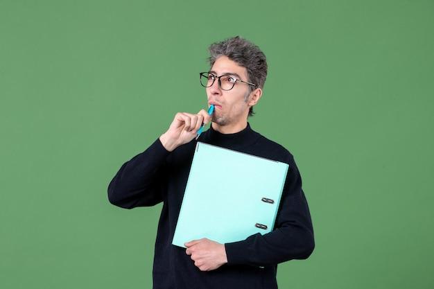 녹색 배경 직업 교사 사업에 문서 스튜디오 촬영을 들고 젊은 남자의 초상화