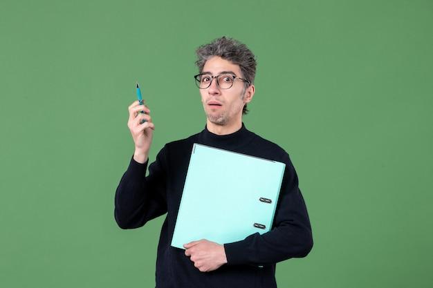녹색 배경 직업 교사 남성에 총에 문서 스튜디오를 들고 젊은 남자의 초상화