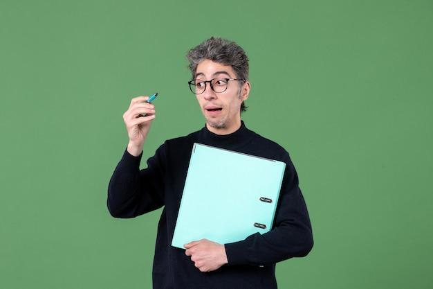 녹색 배경 직업 교사 작업 수업에 문서 스튜디오 촬영을 들고 젊은 남자의 초상화
