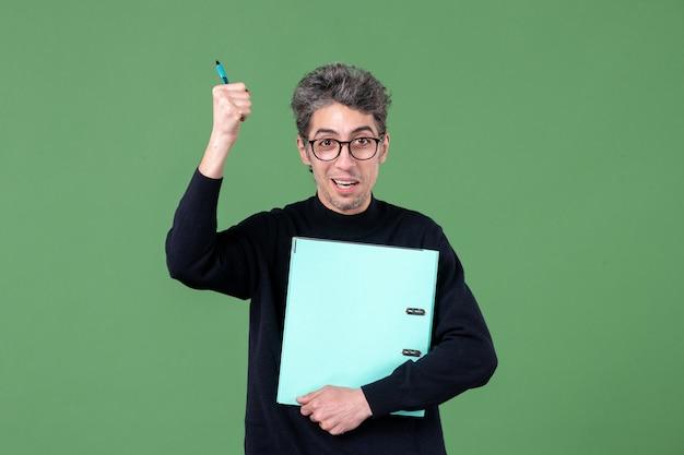 녹색 배경 수업 비즈니스 작업 교사에 촬영 문서 스튜디오를 들고 젊은 남자의 초상화