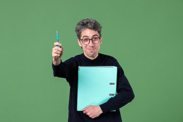 녹색 배경 수업 작업 비즈니스 교사에 문서 스튜디오 촬영을 들고 젊은 남자의 초상화