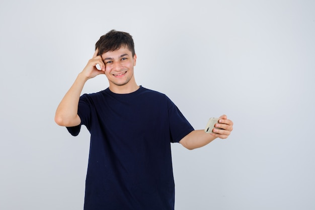 携帯電話を持って、黒いtシャツでポーズを考えて立って、陽気な正面図を見て若い男の肖像画