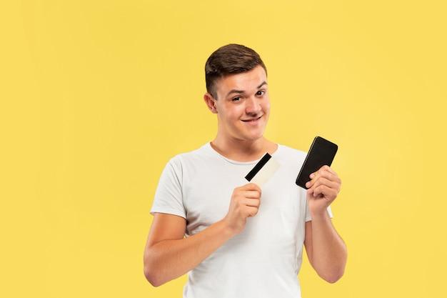 黄色の壁に分離されたスマートフォンとクレジットカードを保持している若い男の肖像画