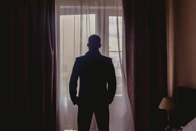 ホテルの部屋の窓に立っているエレガントなスーツを着た若い男の肖像画。男性のための結婚式の朝。輪郭の光のインテリアルームの新郎。背面図。著作権スペース