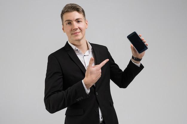 白で隔離される空白の画面を持つ指携帯電話を示す黒のスーツの若い男の肖像