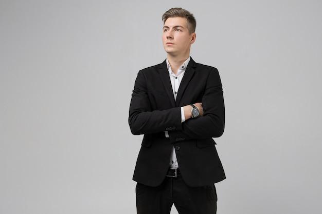 腕を組んで分離白と黒のスーツの若い男の肖像