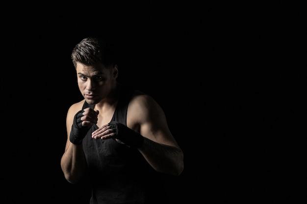 ボクシングのスタンスでポーズをとってボクシングラップで若い男の肖像画