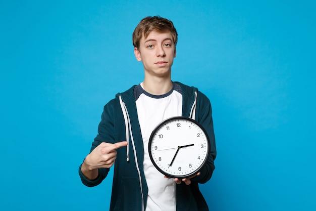 Портрет молодого человека в повседневной одежде, указывая указательным пальцем на круглые часы, изолированные на синей стене. время уходит. концепция образа жизни искренние эмоции людей.