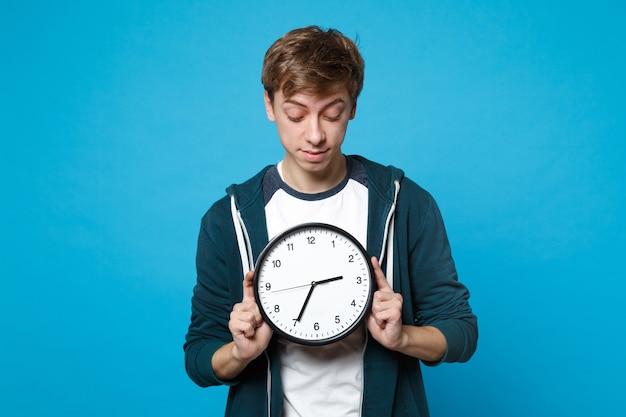 Портрет молодого человека в холдинге повседневной одежды, глядя на круглые часы, изолированные на синей стене. время уходит. люди искренние эмоции, концепция образа жизни.