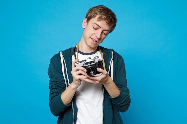파란색 벽에 고립 된 레트로 빈티지 사진 카메라에 사진을 찍고 캐주얼 옷에 젊은 남자의 초상화. 사람들이 성실한 감정 라이프 스타일 개념.