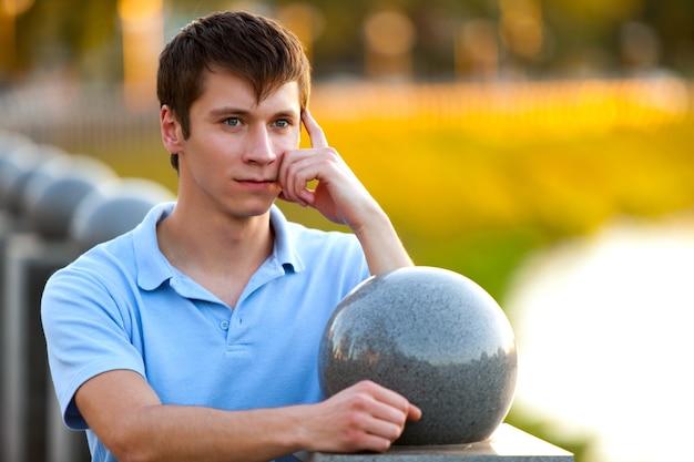캐주얼 의류 서 및 여름 맑은 날에 흐린 배경 위에 뭔가에 대해 생각에 젊은 남자의 초상화. 내면의 자유와 행복한 라이프 스타일 컨셉