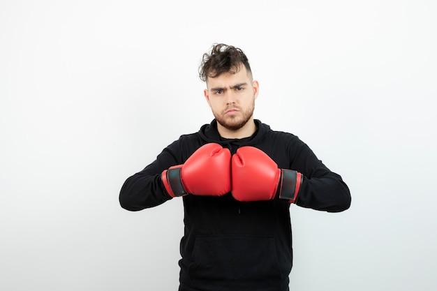 立って見ている赤いボクシンググローブの若い男の肖像画。
