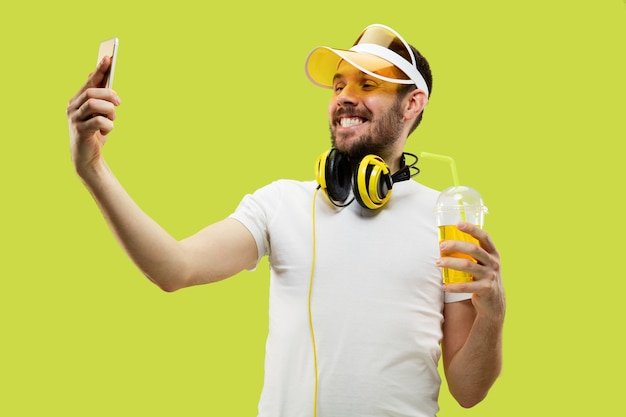 シャツを着た若い男の肖像画。ヘッドフォンと飲み物を持つ男性モデル。人間の感情、表情、夏、週末のコンセプト。自撮り写真を作る。