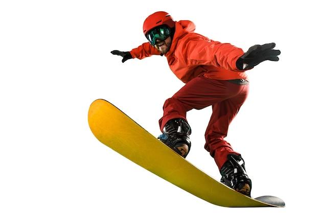 흰색 스튜디오 배경에 격리된 스노보드와 함께 운동복을 입은 젊은 남자의 초상화. 겨울, 스포츠, 스노보드, 스노보더, 활동, 익스트림 컨셉