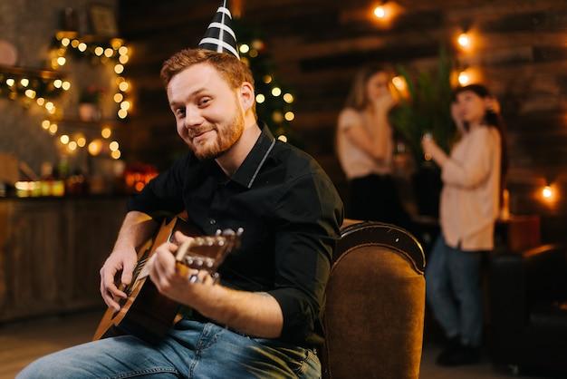 Портрет молодого человека в праздничной шляпе, играющего на гитаре на фоне говорящих друзей. рождественская елка с гирляндой и стеной с праздничным освещением в фоновом режиме.