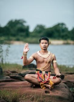 Портрет молодого человека в традиционном костюме, позирующего на природе в таиланде