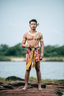 タイの自然の中でポーズをとる伝統的な衣装で若い男の肖像画