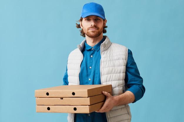 Портрет молодого человека в униформе, доставляющего пиццу, он смотрит в камеру, стоя на синем фоне