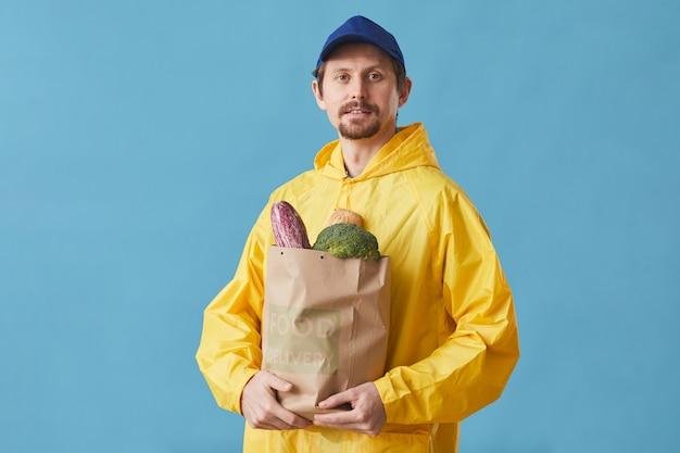 Портрет молодого человека в форме, держащего бумажный пакет с продуктами на синем, он доставляет еду