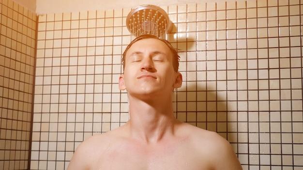 Портрет молодого человека принимает душ, расчесывая волосы руками