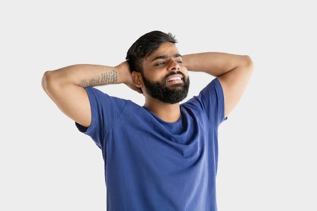 Портрет молодого человека, изолированного на белой стене студии