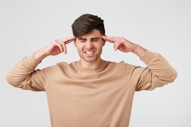Портрет молодого человека, изолированного на белой стене, страдает от сильной головной боли, прижимая пальцы к виску