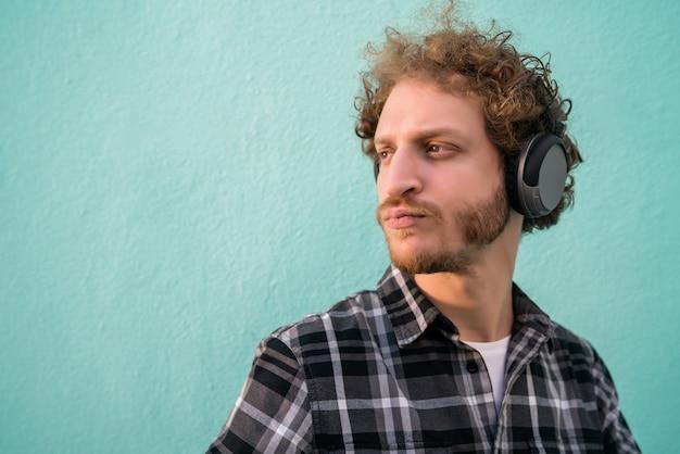 水色の背景にヘッドフォンで音楽を聴いている若い男の肖像画。ライフスタイルのコンセプト。