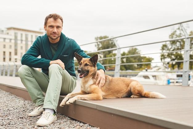 Портрет молодого человека, смотрящего в камеру, сидя со своей собакой на улице на открытом воздухе