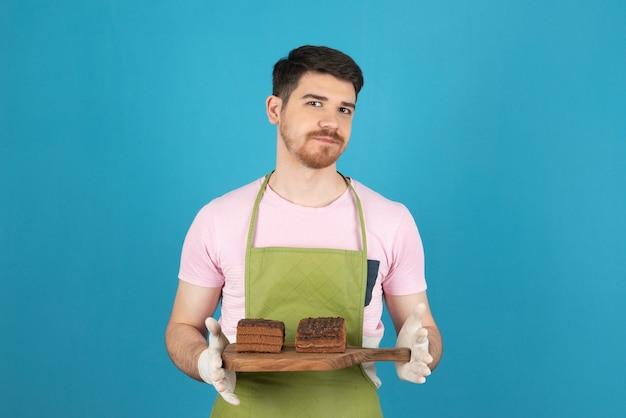 ケーキのスライスを保持している青い上の若い男の肖像画。