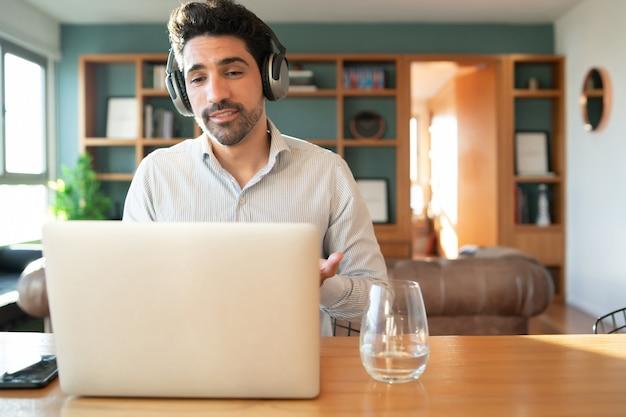 自宅からラップトップで仕事のビデオ通話中の若い男の肖像画。ホームオフィスのコンセプト。新しい通常のライフスタイル。