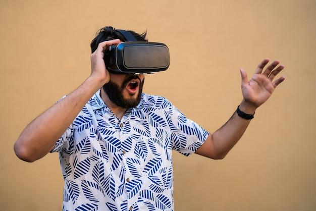 黄色の背景に対して仮想現実のvrヘッドセットメガネで遊んでいる若い男の肖像画。 vrヘッドセットメガネデバイス。技術コンセプト。