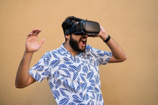 Портрет молодого человека, играющего с очками виртуальной реальности vr-гарнитуры против желтого пространства. устройство для очков виртуальной реальности. концепция технологии.