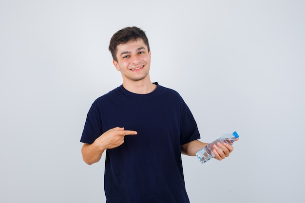 검은 티셔츠에 물 한 병을 가리키고 자신감이 전면보기를 찾고 젊은 남자의 초상화