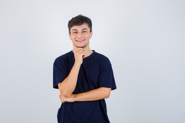 黒のtシャツで手に顎を支え、陽気な正面図を探している若い男の肖像画