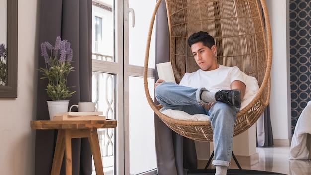 Портрет молодого человека расслабляющий и читающий книгу, сидя в удобном кресле у себя дома.