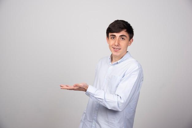 Портрет молодого человека показывая космос экземпляра на его ладони на серой стене.