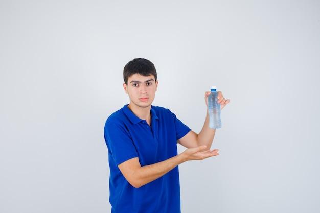 Портрет молодого человека, показывающего пластиковую бутылку в футболке и уверенно выглядящего, вид спереди