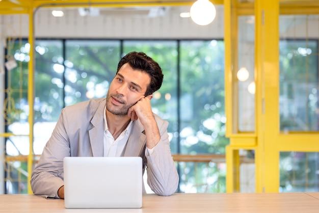 現代のオフィスの彼の机に座っている若い男の肖像画、ラップトップ思考で働く焦点を絞った実業家