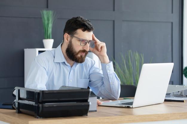 オフィスの彼の机に座っている若い男の肖像